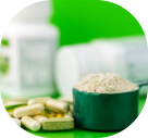 food supplement pills and protein powder in plastic spoon on green background
