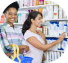 portrait of confident women smiling while friend choosing product in pharmacy